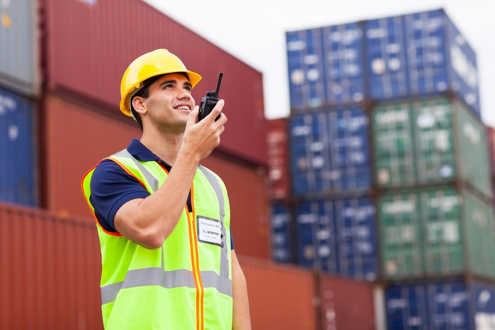 Port worker on radio amongst shipping containers